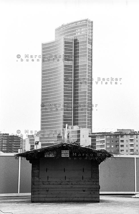 """Milano, progetto di riqualificazione dell'area di Porta Nuova. Veduta dal """"Podio"""" (Piazza Gae Aulenti) verso Palazzo Lombardia, sede della giunta regionale. In primo piano, una casetta in legno per attività commerciali --- Milan, requalification project of """"Porta Nuova"""" area. View from the """"Podio"""" (Gae Aulenti square) towards """"Palazzo Lombardia"""", headquarter of Lombardy regional authority. In the foreground, a small wooden house for commercial activity"""