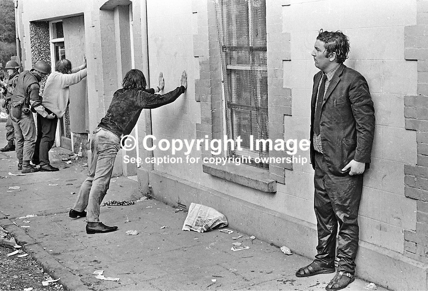 A drenched John Hume waits to be searched by British soldiers following the military use of a water cannon to break up a civil rights sit-down protest in the Nationalist Bogside area of Londonderry on 26th August 1971. John Hume at the time was the sitting SDLP MP in the N Ireland Parliament at Stormont.  To the left a soldier can be seen searching Hume's fellow SDLP MP, Ivan Cooper. 197108260001<br /> <br /> Copyright Image from Trevor McBride c/o<br /> Victor Patterson, 54 Dorchester Park, Belfast, UK, BT9 6RJ<br /> <br /> t1: +44 28 9066 1296 (from Rep of Ireland 048 9066 1296)<br /> t2: +44 28 9002 2446 (from Rep of Ireland 048 9002 2446)<br /> m: +44 7802 353836<br /> <br /> e1: victorpatterson@me.com<br /> e2: victorpatterson@gmail.com<br /> <br /> The use of any of my copyright images is subject to my Terms &amp; Conditions. It is IMPORTANT that you familiarise yourself with them. They are available at my website, victorpatterson.com.<br /> <br /> None of my copyright images may be used on the Internet unless they are visibly watermarked, i.e. &copy; Victor Patterson within the body of the image. My metadata, denoting my copyright must NOT be deleted. <br /> <br /> Web use is extra at currently recommended NUJ rates. Maximum permitted web size is<br />  400kb. <br /> <br /> Images must not be passed on to a third party - they are for the use of the authorised recipient only.