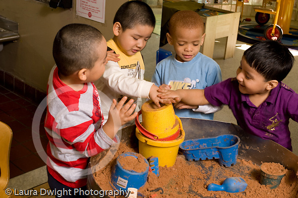 Preschool Headstart 3-5 year olds sand table group of boys playing together horizontal