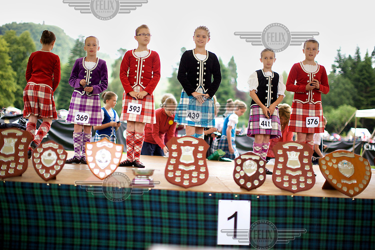 Young girls stand behind trophies in a Highland dancing competition at the Inveraray Highland Games, held at Inveraray Castle in Argyll.