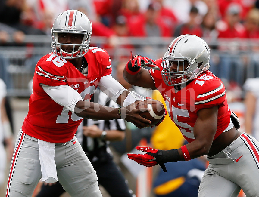 Ohio State Buckeyes quarterback J.T. Barrett (16) hands off the ball to Ohio State Buckeyes running back Ezekiel Elliott (15) during Saturday's NCAA Division I football game against the Kent State Golden Flashes at Ohio Stadium in Columbus on September 13, 2014. Ohio State won the game 66-0. (Dispatch Photo by Barbara J. Perenic)