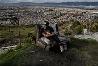 BOGOTA - COLOMBIA, 27-05-2020: Joven observa colina abajo sobre un sofá sacado al aire libre en el barrio Altos de La Estancia. Mas de 200 familias terminan el proceso de desalojo en el predio La Estancia al sur de Bogotá quedando sin ninguna ayuda ni un techo donde vivir durante la cuarentena total en el territorio colombiano causada por la pandemia  del Coronavirus, COVID-19. / Young man watches down the hill on an outdoor sofa in the Altos de La Estancia neighborhood. More than 200 families are evicted from La Estancia farm at south of Bogota city and they left withoput any help and shelter to live during total quarantine in Colombian territory caused by the Coronavirus pandemic, COVID-19. Photo: VizzorImage / Mariano Vimos / Cont