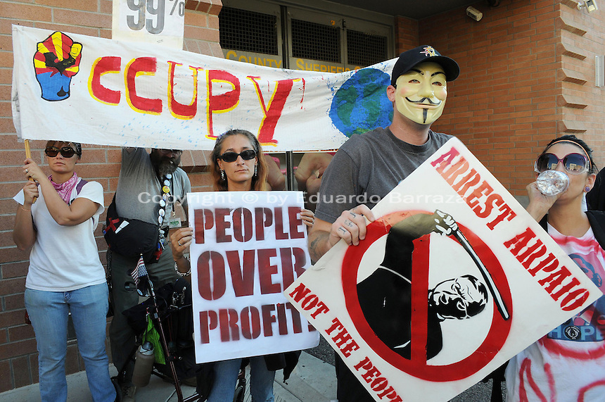 Phoenix, Arizona. September 17, 2012 - A small crowd of demonstrators in Phoenix, Arizona gathered to mark one year since the beginning of the Occupy Movement that opposes Wall Street and large corporations that represent the one percent who control wealth in the United States. In this photograph, a group of activists with the Occupy Phoenix group demonstrates outside the Fourth Avenue Maricopa County Jail in Downtown Phoenix. Photo by Eduardo Barraza © 2012