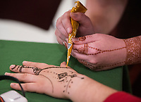 NWA Democrat-Gazette/BEN GOFF @NWABENGOFF <br /> Kristi Brixey, Northwest Arkansas Community College international programs technician, paints a henna design on the hand of student Maria Martinez Thursday, Nov. 15, 2018, at Northwest Arkansas Community College in Bentonville. The community college is celebrating International Education Week with events including movie screenings, food, yoga classes and a silent auction which ends Friday. Proceeds from the auction support scholarships for international students and other programs.