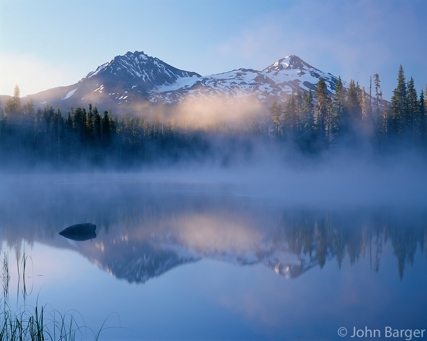 ORCAC_113 - USA, Oregon, Willamette National Forest, North (left) and Middle Sister (right) reflect in Scott Lake at sunrise while fog swirls above the lake.