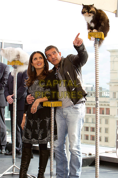 "Salma Hayek & Antonio Banderas.At the photocall for ""Puss In Boots"", Moscow, Russia, 26th September 2011..full length hand finger pointing gesture  arm around black  hand fist funny gesture knee high boots jeans cat animal .CAP/PER/SB.©SB/PersonaStars/Capital Pictures."