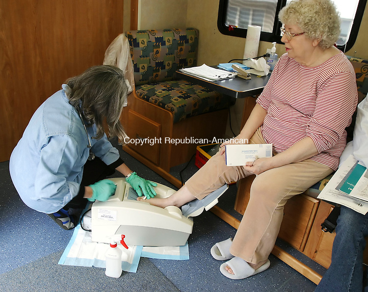 SEYMOUR, CT 4/2/07- 040207BZ11- Daun Barrett, (CQ) R.N., director of community outreach and parish nursing at Griffin Hospital, left, uses an &quot;Achilles InSight&quot; machine to check the bone density of Pat Thompson, of Seymour, during a screening at the Norman L. Ray House in Seymour Monday.<br /> Jamison C. Bazinet Republican-American