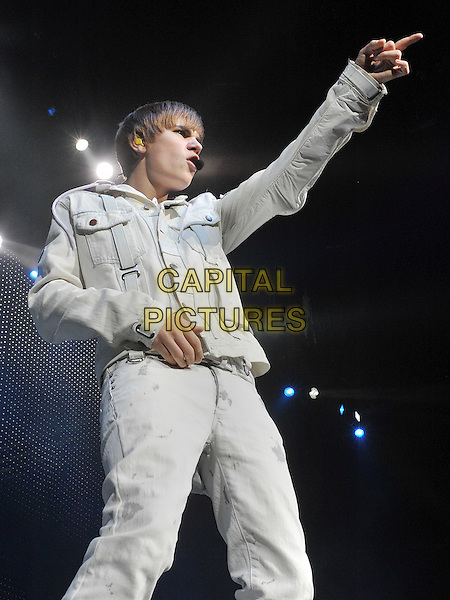 """JUSTIN BIEBER .Justin Bieber performs to a sold outcrowd at a stop on his """"""""My World Tour 2010"""" held at the Consol Energy Center, Pittsburgh, PA, USA.    .December 13th, 2010                .stage concert live gig performance music half 3/4 length white jean denim jacket hand arm pointing singing hand foot leg up.CAP/ADM/JN.©Jason L Nelson/AdMedia/Capital Pictures."""