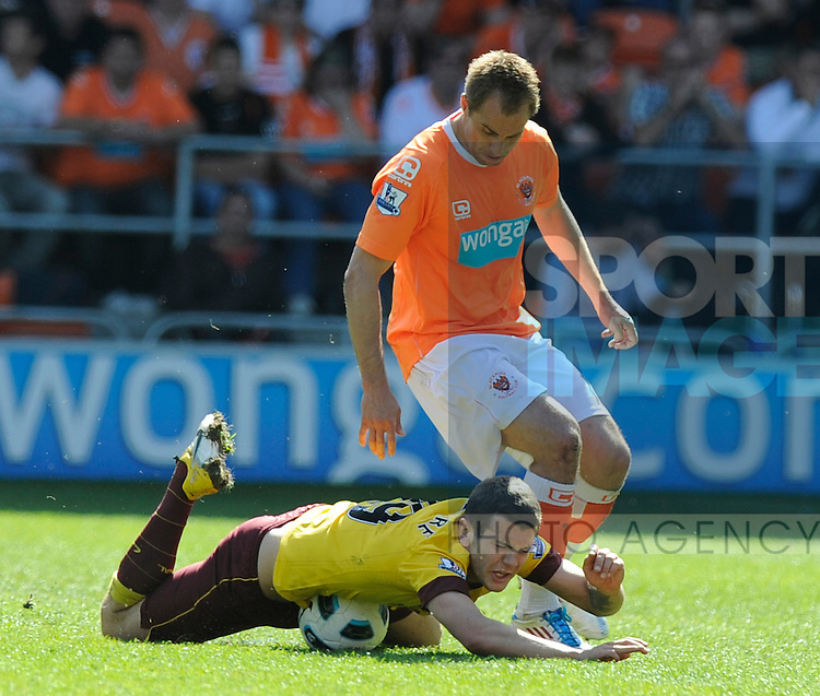Jack Wilshere of Arsenal tackled by Luke Varney of Blackpool