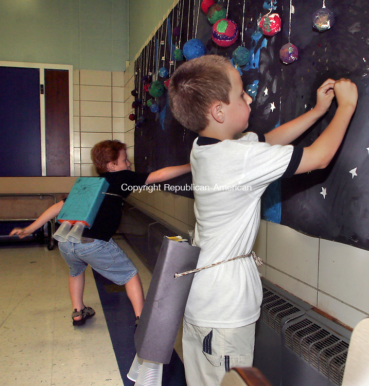 WINSTED, CT.- 22 JULY 2009-07239DA01- Devon Devanney, 6, right, puts a star on a space mural along side of Jacob Harrison, 6, take part in a race wearing their space packs they made Thursday during one week  a &quot;space&quot; program for kids in kindergarden through fifth grade held at St. Anthony's School in Winsted.<br />  Darlene Douty Republican-American