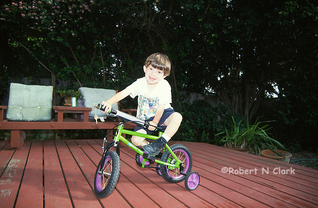 Boy on first bike with training wheels