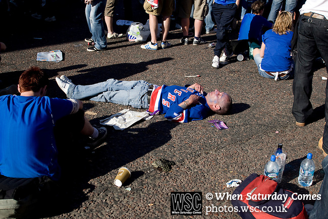 Rangers Fans in Manchester, 14/05/2008. Albert Square, UEFA Cup Final. A fan of Glasgow Rangers sleeping on a road in the centre of Manchester as supporters gather to watch the UEFA Cup final against Zenit St. Petersburg on a large screen in Albert Square, the location of one of the UEFA Fan Zones. The match was staged at the City of Manchester Stadium and was won by the Russian team by two goals to nil. It was Rangers' first European final appearance since they won the Cup-Winners Cup in 1972 and around 150,000 fans gathered in Manchester. Photo by Colin McPherson.