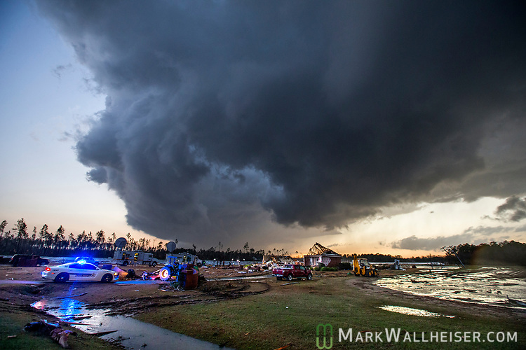 Storm clouds approach emergency crews at the scene of a house cut in half by a tornado near where seven people were killed outside Adel, Georgia USA on 22 January 2017. Emergency officials report that at least eleven people have been killed in Georgia during a severe weather outbreak in the southern United States.  (Mark Wallheiser/EPA)