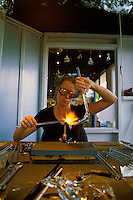 A glass artist  woman) demonstrates her skills to onlookers at one of the many shops located at the Northshore Marketplace in the town of Haleiwa on Oahu's north shore.