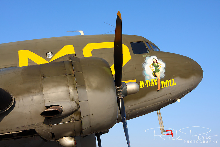 A Douglas C-54D Skytrooper dressed in a D-Day paint scheme sits on the ramp at Minter Field in Central California. The aircraft was flown in from its home airport in Riverside, California, where it is part of the Inland Empire Wing of the Commemerative Air Force, for the 2008 Warbirds In Action air show. One of 221 built The C-54D is based on the Douglas DC-3\C-47 airframe with the addition of 28 fixed seats and a towing cleat for use as a glider tug. Photographed 04/08