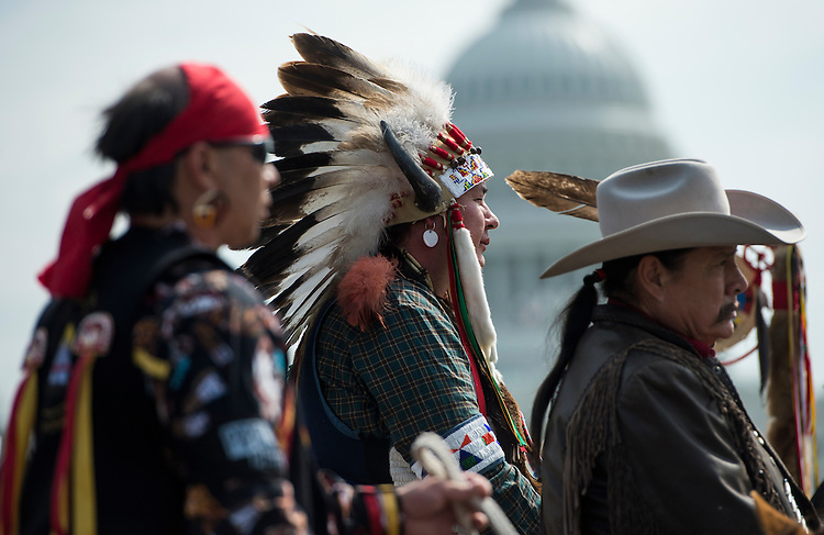 """UNITED STATES - APRIL 22: Indigenous leaders from the Cowboy and Indian Alliance watch form their horses as tribal leaders host a traditional opening ceremony to begin their ride from the Capitol to their camp on the National Mall to protest The Kesystone XL Pipeline on Tuesday, April 22, 2014. 24 ranchers and indigenous leaders from the Cowboy and Indian Alliance rode their horses from the Capitol to the Reject and Protect encampment on the National Mall for a week's worth of """"Reject and Protect"""" actions against the Keystone XL tar sands pipeline.  (Photo By Bill Clark/CQ Roll Call)"""