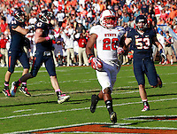 Oct. 22, 2011 - Charlottesville, Virginia - USA; North Carolina State Wolfpack running back Tony Creecy (26) runs in for a touchdown in front of Virginia Cavaliers defenders during an NCAA football game at the Scott Stadium. NC State defeated Virginia 28-14. (Credit Image: © Andrew Shurtleff