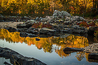 Reflections at Cossatot Falls in the fall. Located in southwest Arkansas south of Mena, the Cossatot river forms Cossatot Falls, a rugged and rocky canyon that challenges the most experienced canoeists and kayakers with its Class IV and V rapids.