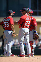 St. Louis Cardinals manager Mike Matheny (22) talks with third baseman Daniel Descalso (33) and catcher Audry Perez during a pitching change during a spring training game against the Detroit Tigers on March 3, 2014 at Joker Marchant Stadium in Lakeland, Florida.  Detroit defeated St. Louis 8-5.  (Mike Janes/Four Seam Images)