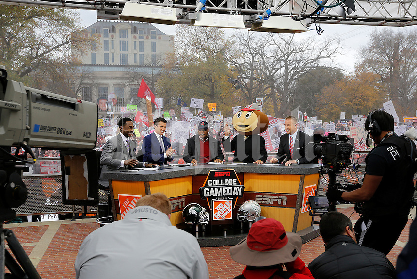 Lee Corso waves while wearing a Brutus Buckeye head as, from left, Desmond Howard, Rece Davis, Archie Griffin, and Kirk Herbstreit applaud his pick during ESPN's College GameDay broadcast from the campus of Ohio State prior to the NCAA football game against the Michigan State Spartans in Columbus on Nov. 21, 2015. (Adam Cairns / The Columbus Dispatch)
