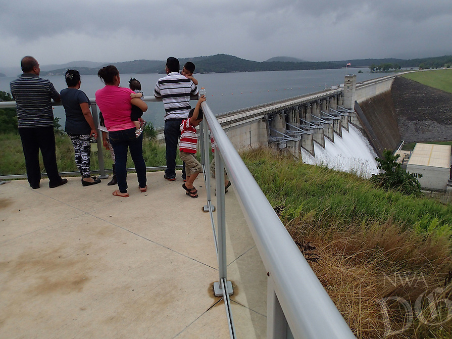 NWA Democrat-Gazette/FLIP PUTTHOFF<br /> Visitors view the open flood gates July 9 2015 at Beaver Dam from an overlook on the dam's south side. The overlook was recently remodeled and includes information panels about the dam and lake.