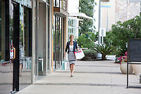 Beautiful woman shopper with many shopping bags walks down the sidewalk at an Austin outdoor shopping center