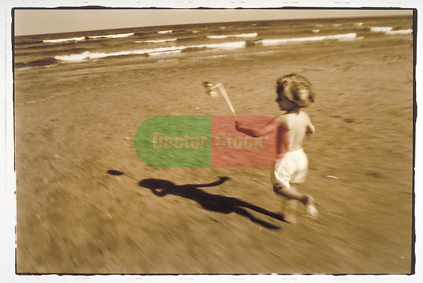 young boy running on beach with pinwheel