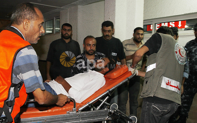 Palestinians wheel a wounded man following an Israeli attack in Gaza City on August 19, 2011. Photo by Mahmud Nassar