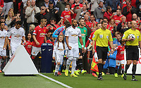 Pictured: The teams led by the match officials enter the pitch. Saturday 16 August 2014<br />