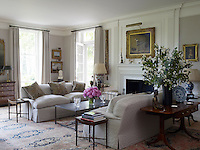 French windows lead from the triple aspect drawing room to a terrace overlooking the garden