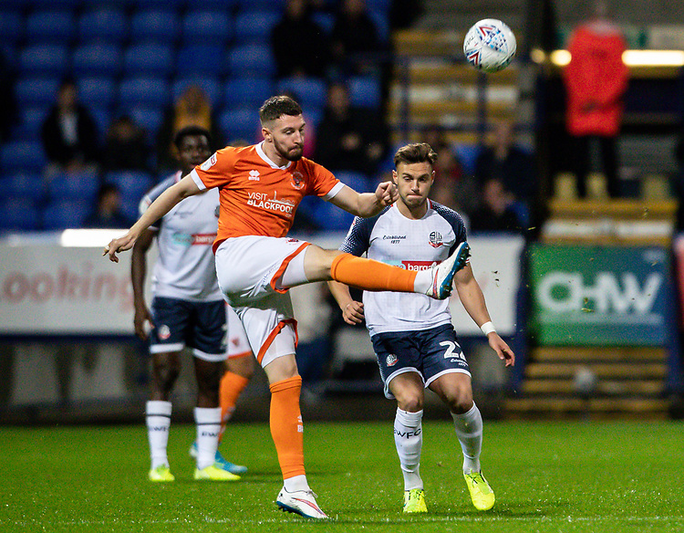 Bolton Wanderers' Dennis Politic (right) looks on as Blackpool's James Husband clears<br /> <br /> Photographer Andrew Kearns/CameraSport<br /> <br /> The EFL Sky Bet League One - Bolton Wanderers v Blackpool - Monday 7th October 2019 - University of Bolton Stadium - Bolton<br /> <br /> World Copyright © 2019 CameraSport. All rights reserved. 43 Linden Ave. Countesthorpe. Leicester. England. LE8 5PG - Tel: +44 (0) 116 277 4147 - admin@camerasport.com - www.camerasport.com