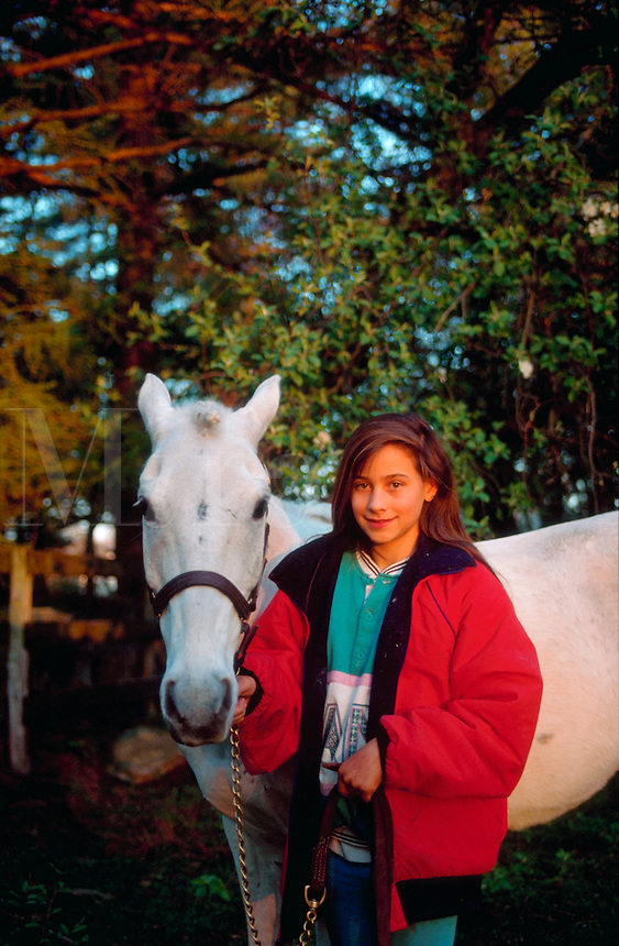 Teen girl posing with her white horse.