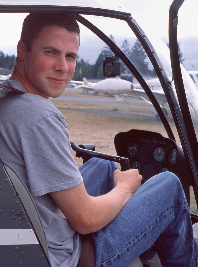 A male pilot sits in the cockpit of a Robinson R22 helicopter.