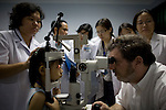 Dr. James Brandt, of Sacramento, examines Nhi Uyen Luong, 7, who suffers from glaucoma, while Vietnamese doctors Tien Thuy Thi Pham, left, and Tam Dang Mai, left, study the child's case. Photo taken at the Ho Chi Minh City Eye Hospital on Monday, April 14, 2008. Kevin German /  kevin@kevingerman.com..ORBIS Flying Eye Hospital brought doctors, nurses and specialists from all over the world to Ho Chi Minh City, Vietnam from April 7-18, 2008.  The ORBIS program contributed to the efforts of Ho Chi Minh City Eye Hospital in fighting avoidable blindness by educating local ophthalmologists to diagnose and manage pediatric blindness, retinal disease, oculoplastics, and blindness due to glaucoma.