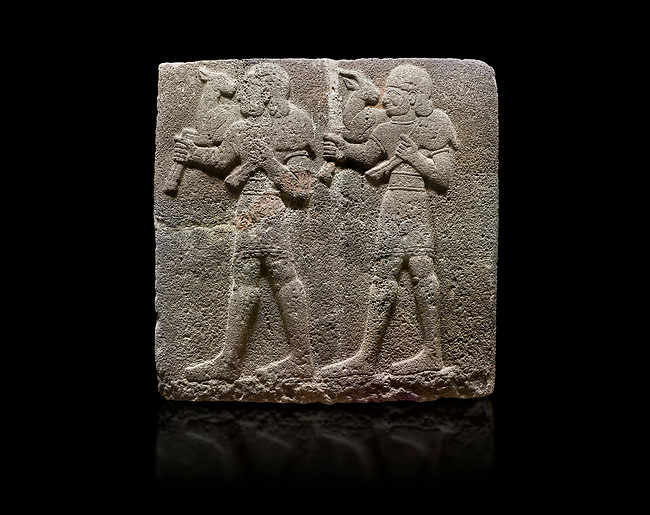 Hittite monumental relief sculpted orthostat stone panel of a Procession Basalt, Karkamıs, (Kargamıs), Carchemish (Karkemish), 900-700 B.C.  Anatolian Civilisations Museum, Ankara, Turkey. Young male servants of Kubaba while carrying sacrificial animals on their shoulders. <br /> <br /> Against a black background.