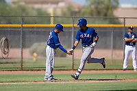 Texas Rangers third baseman Tyler Ratliff (32) is congratulated by his third base coach during an Instructional League game against the San Diego Padres on September 20, 2017 at Peoria Sports Complex in Peoria, Arizona. (Zachary Lucy/Four Seam Images)