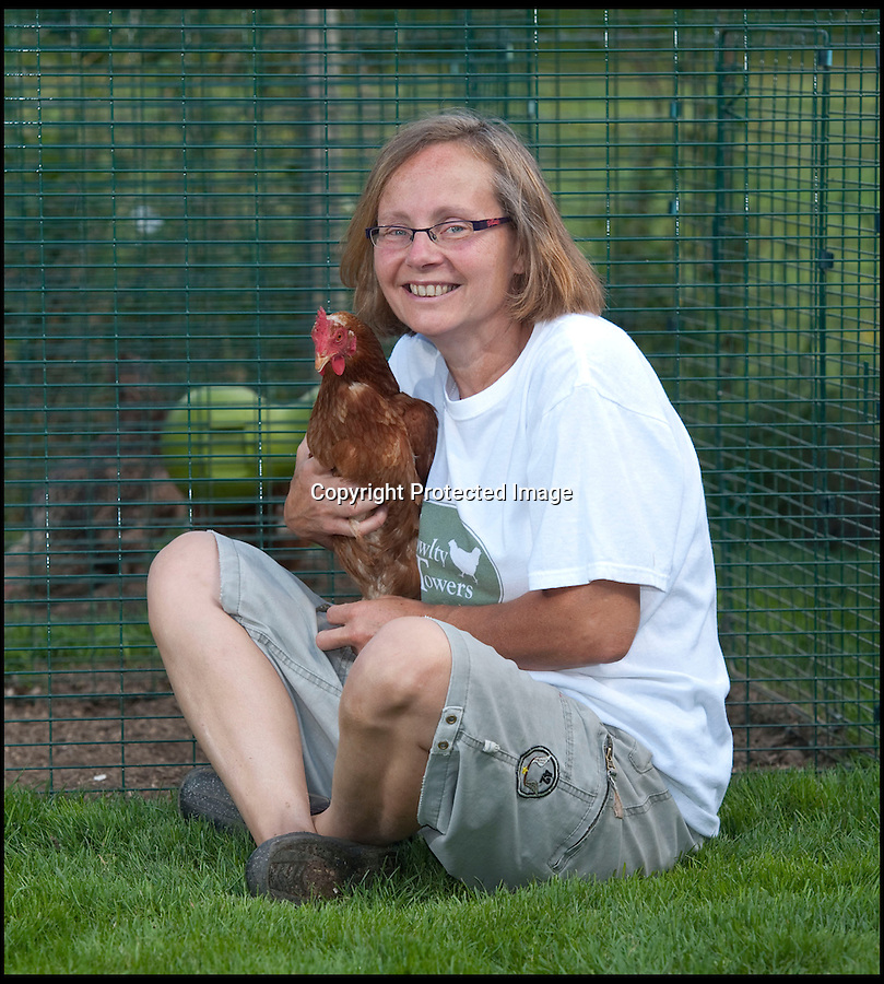 BNPS.co.uk (01202 558833)<br /> Pic: PhilYeomans/BNPS<br /> <br /> Julie and guest in the Eglu coop.<br /> <br /> Fowlty Towers - Egg-ceptional new hotel for hens.<br /> <br /> The boom in hen keeping across Britain has led a canny Kent lady to spotting a gap in the market for a deluxe hotel for punters beloved poultry whilst they jet off on their summer hols. <br /> <br /> Julie Smith from Cowden is inundated with requests for 'rooms' at 'Fowlty Towers', with customers booking months in advance to secure a spot for their prized birds. <br /> <br /> Julie's all-inclusive resort costs a poultry £7 a night for each run, with round the cluck service including all food and drink.