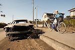 Mar. 13, 2011 - Kita-Ibaraki, Japan - A man walks his bicycle past a car that was caught on fire two days after the 8.9 magnitude earthquake struck followed by a tsunami that hit the north-eastern region. The death toll is currently unknown with casualties that may run well into the thousands.