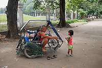 Young child and her father who is a pedi cup driver in Manila, Philippines
