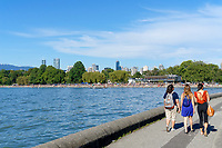 Three young women walking on the Kitsilano seawall path with Kitsilano Beach and English Bay in back, Vancouver, British Columbia, Canada