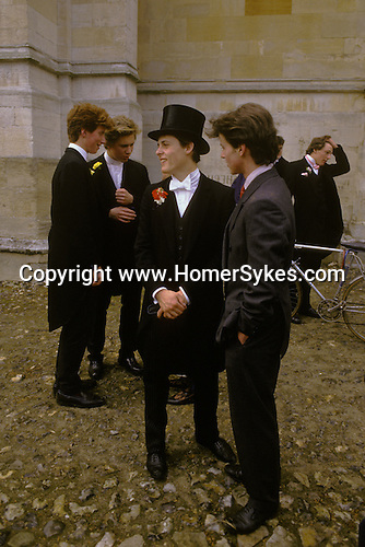 Eton schoolboys in top hats and traditional school uniform. The boy in a grey suit is from Harrow school.  The English Season published by Pavilon Books 1987