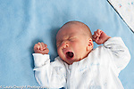3 day old newborn baby boy closeup on back reflex yawning