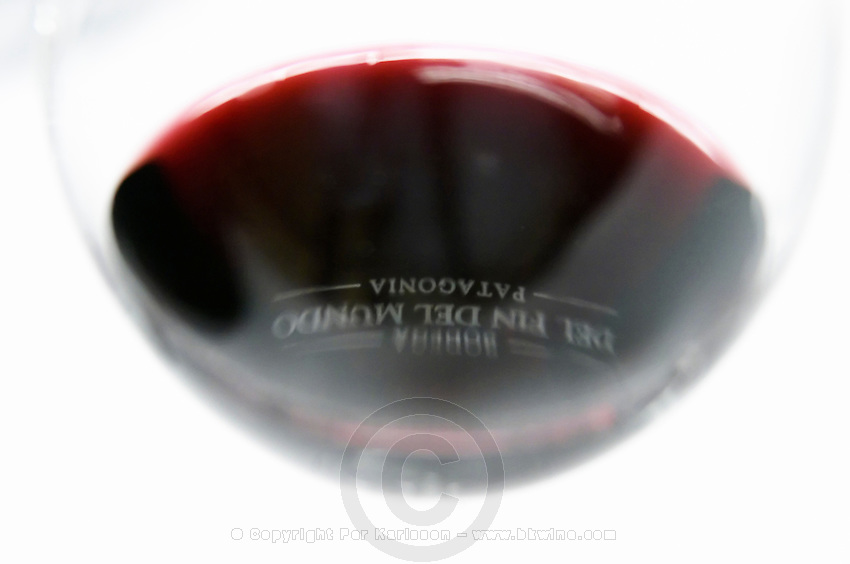 glass of red wine with reflection of the engraved the name of the vineyard against a white background Bodega Del Fin Del Mundo - The End of the World - Neuquen, Patagonia, Argentina, South America