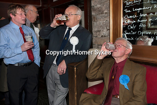 Askrigg Equitable Benevolent and Friendly Society. Askrigg north Yorkshire UK. Members in the bar of the Kings Arms Hotel before the annual walk to church behind the Friendly Society banner. Honorary members wear a white rosette, while ordinary members wear a blue one.