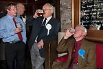 Askrigg Equitable Benevolent and Friendly Society. Askrigg north Yorkshire UK. Members in the bar of the Kings Arms Hotel before the annual walk to church behind the Friendly Society banner. Honorary members wear a white rosette, while ordinary members wear a blue one. 2014