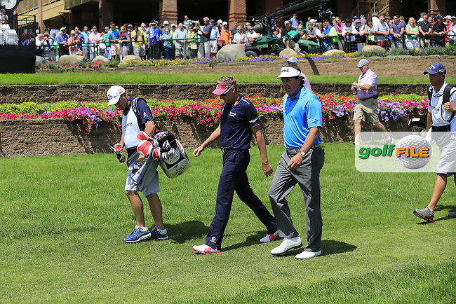 Ian Poulter (ENG) and Phil Mickelson (USA) walk off the 1st tee to start their match during Sunday's Final Round of the 2013 Bridgestone Invitational WGC tournament held at the Firestone Country Club, Akron, Ohio. 4th August 2013.<br /> Picture: Eoin Clarke www.golffile.ie