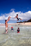 USA, Oahu, Hawaii, father throws his son into the air and into a tide pool at Pipeline Beach on the North Shore
