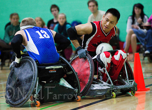 15 AUG 2011 - LEEDS, GBR - Canada's Ian Chan brushes off a challenge from Great Britain's Aaron Phipps to score during the wheelchair rugby exhibition match between the two teams .(PHOTO (C) NIGEL FARROW)