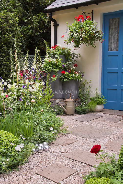 Small pretty entry garden, with house door, hanging basket of flowers, gravel and flagstone walkway path, galvanized containers of different sizes, lush flowers, vertical and tall with low and mounding, different sizes and texture, rustic watering can. Patriotic red, white and blue color theme
