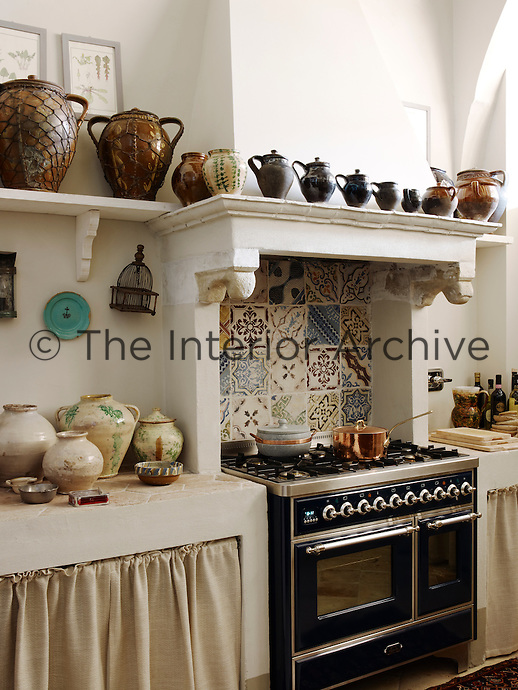 An alcove lined with an assortment of ceramic tiles houses a modern oven which is flanked by bespoke kitchen units with hexagonal tile work surfaces